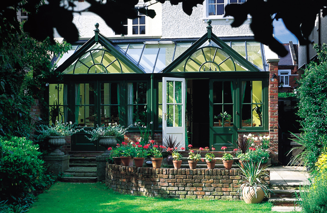 Double gabled timber extension, painted dark green to blend with garden