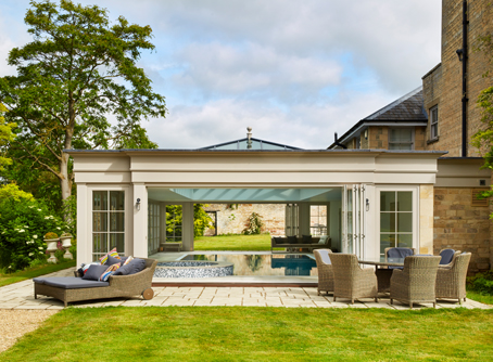 Pool House Extension With Doors Open Onto Outside Seating Area