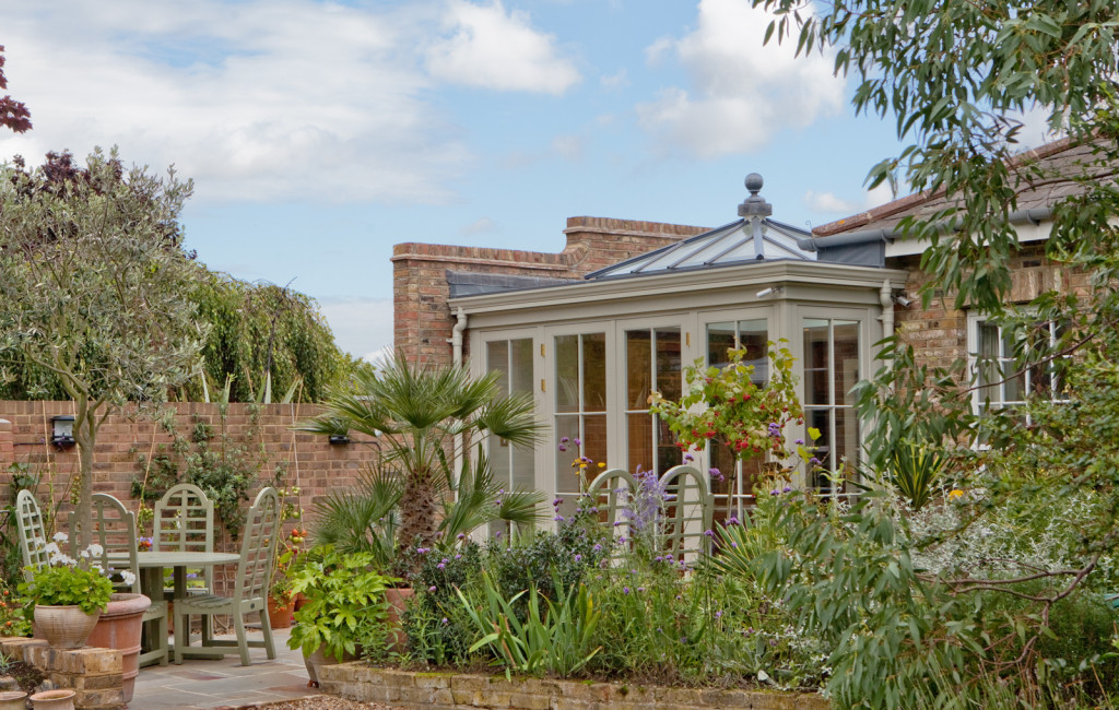 Stunning orangery perfectly blending with house and garden featuring a pyramid lantern