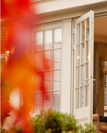 View of an ajar french door opening into an Autumn garden