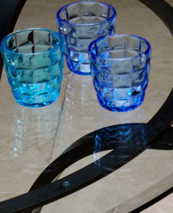 Blue glasses on glass table inside stone floor garden room