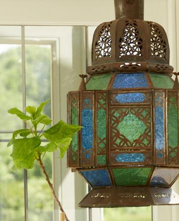 Ornate coloured glass lamp inside orangery window