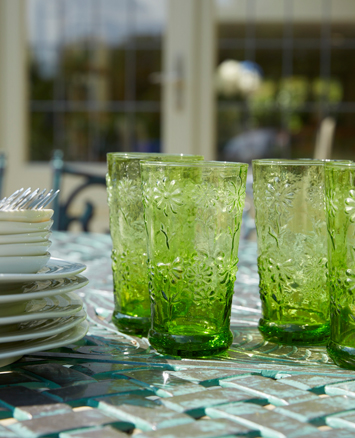 Glasses on an outside table, in front of a garden room