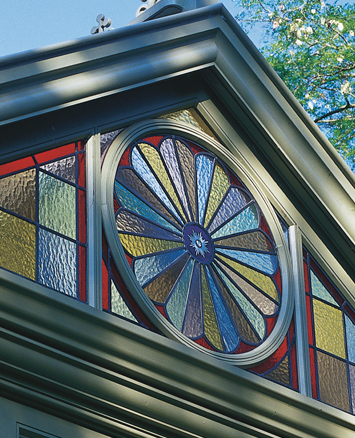 Beautiful multi-coloured stained glass window in orangey gable