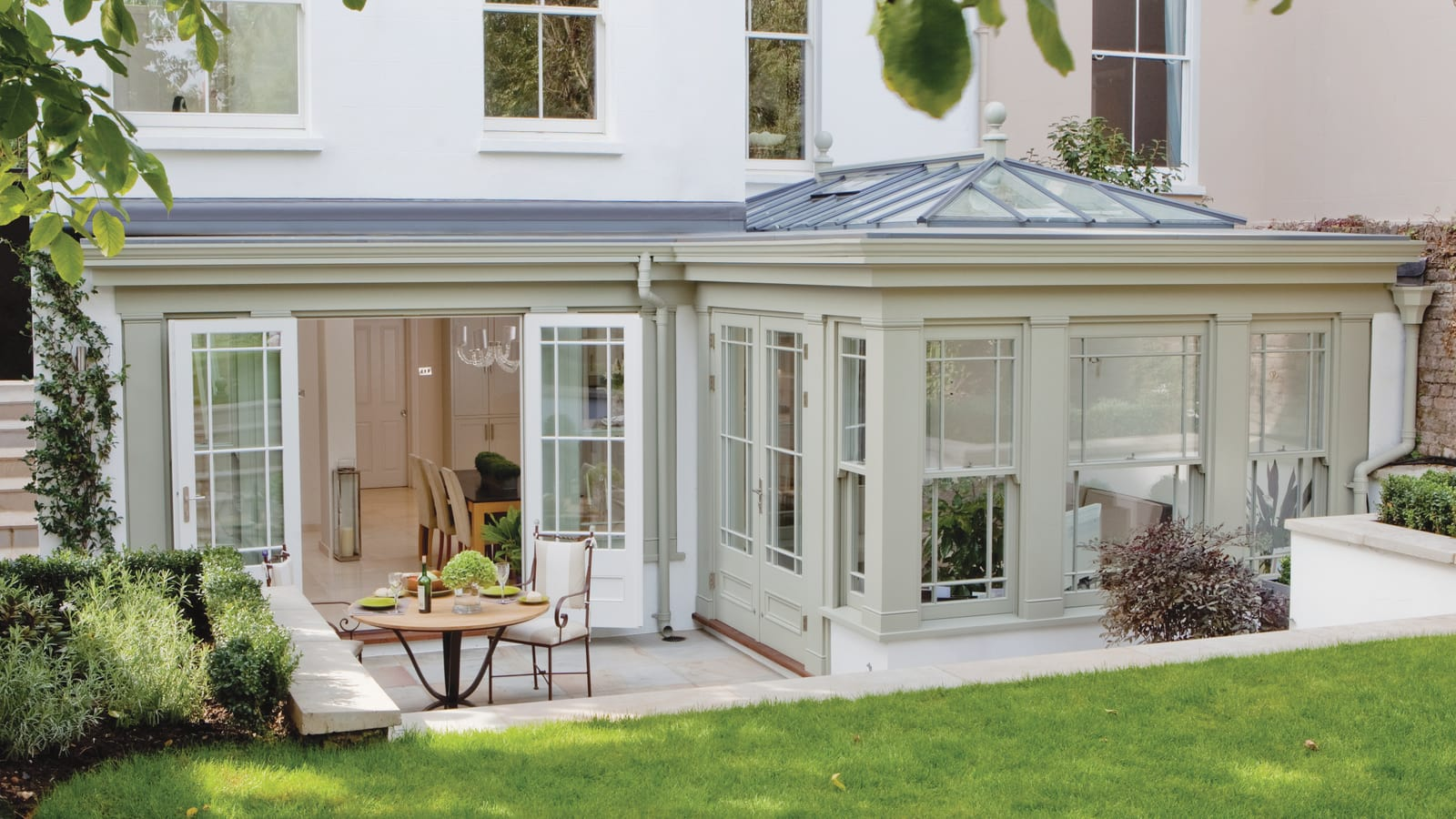 An orangery design featuring sliding sash windows and french doors
