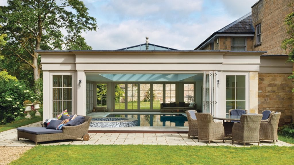 Pool house with three sets of bi-folding doors open all the walls