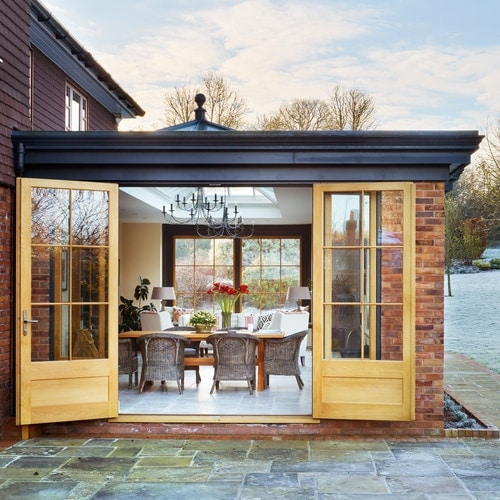 Striking black and oak orangery enhancing the exterior design of this village home