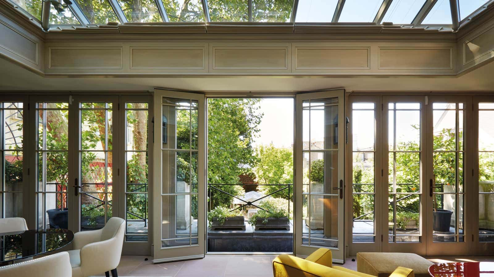 French doors opening on to a balcony offering uninterrupted views of the expansive garden below