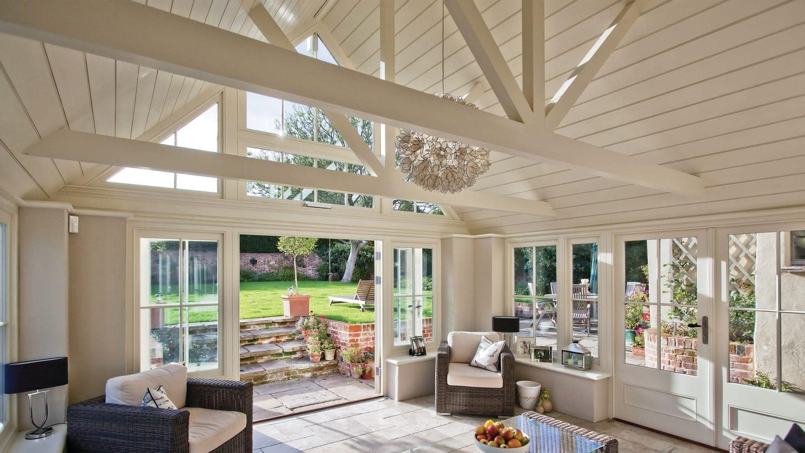 View from inside a spectacular garden room featuring a glazed gable end and french doors