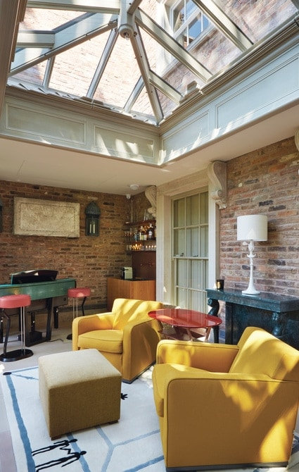 Informal seating area inside orangery with view of roof lantern