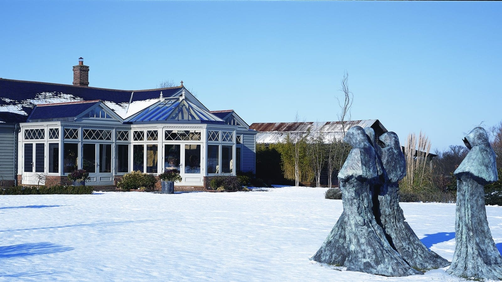 Long shot of glazed timber garden room in the snow