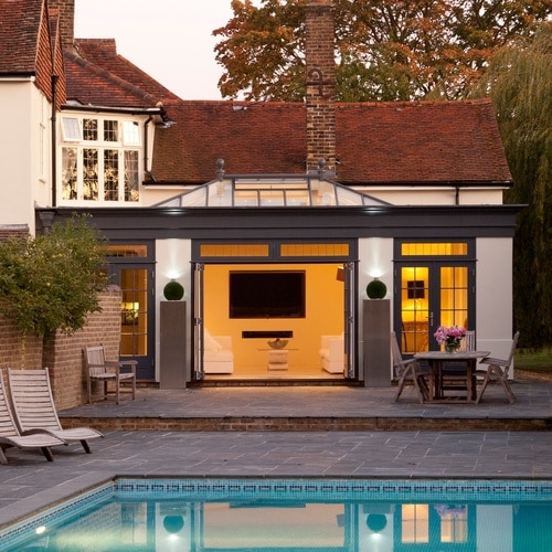 Minimalist extension leading to patio area with swimming pool