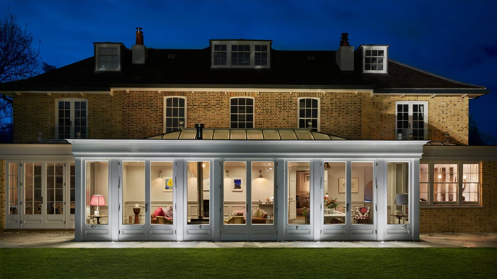 Exterior view of beautifuly lit orangery at dusk