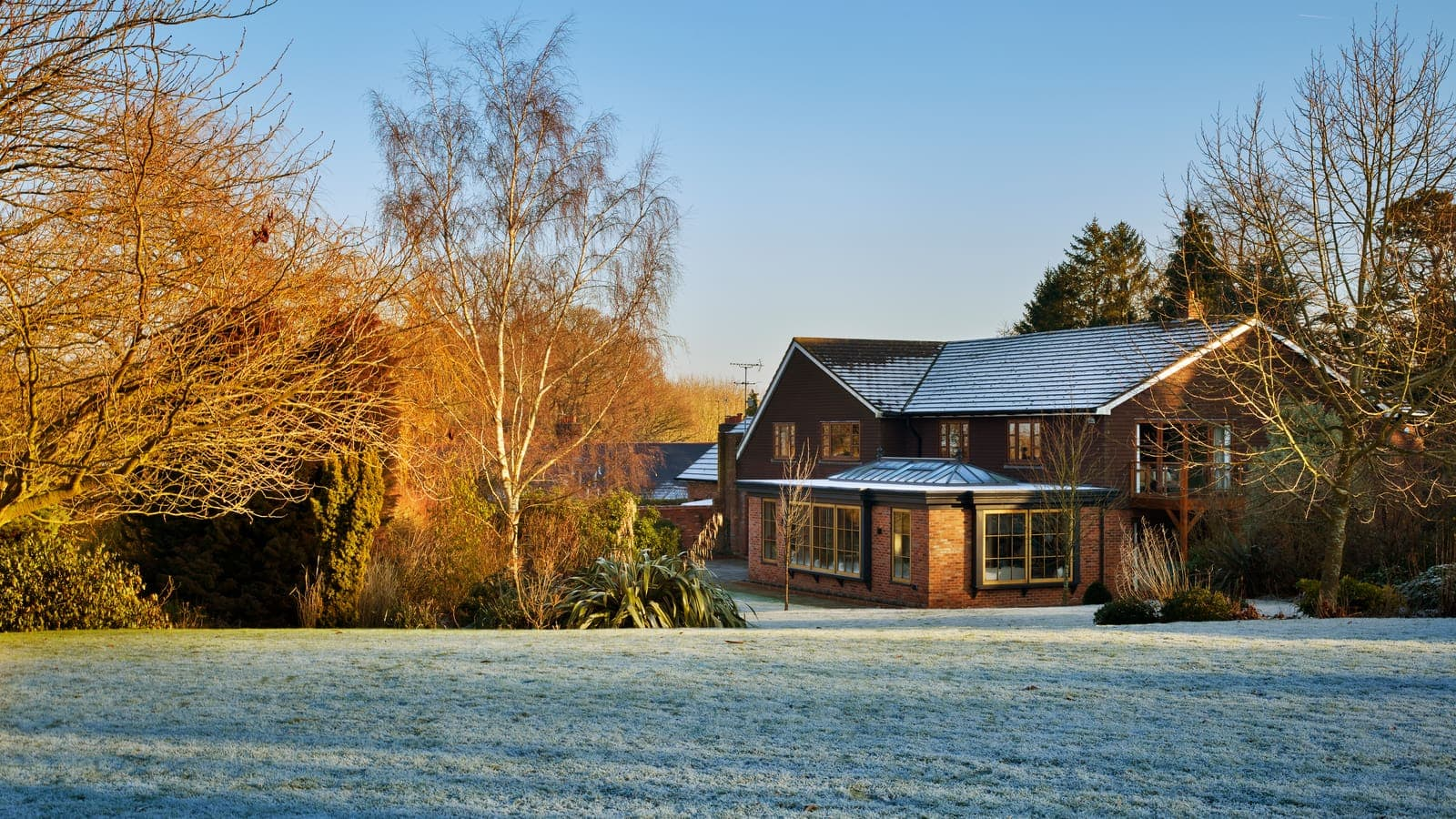 Long shot of orangery extension and grounds on a frosty day