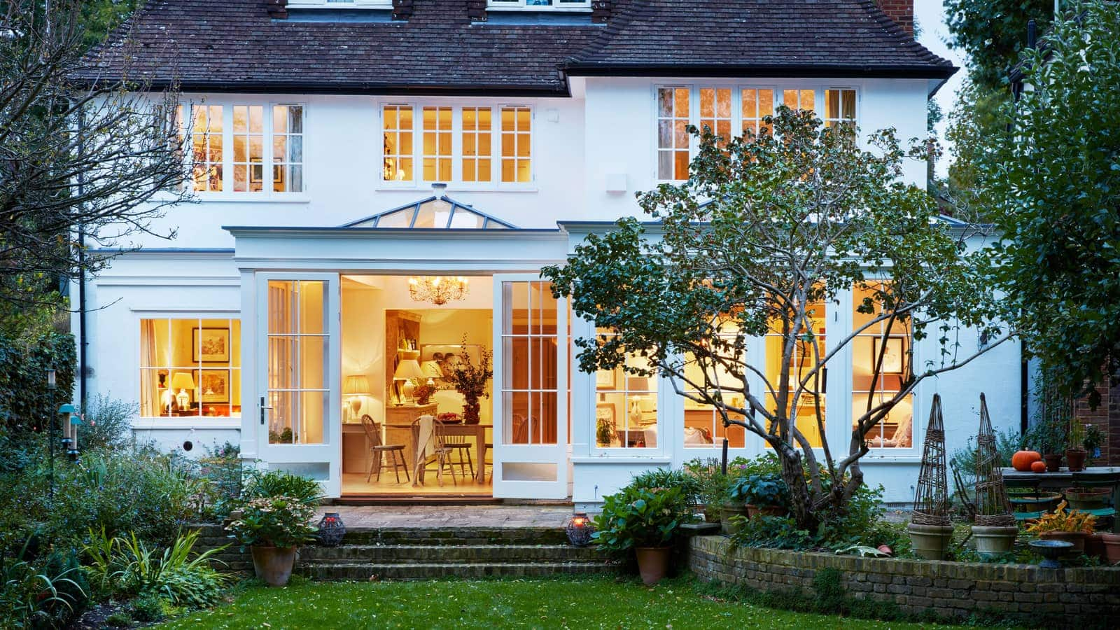 Exterior view of orangery with french doors open on to the garden at dusk