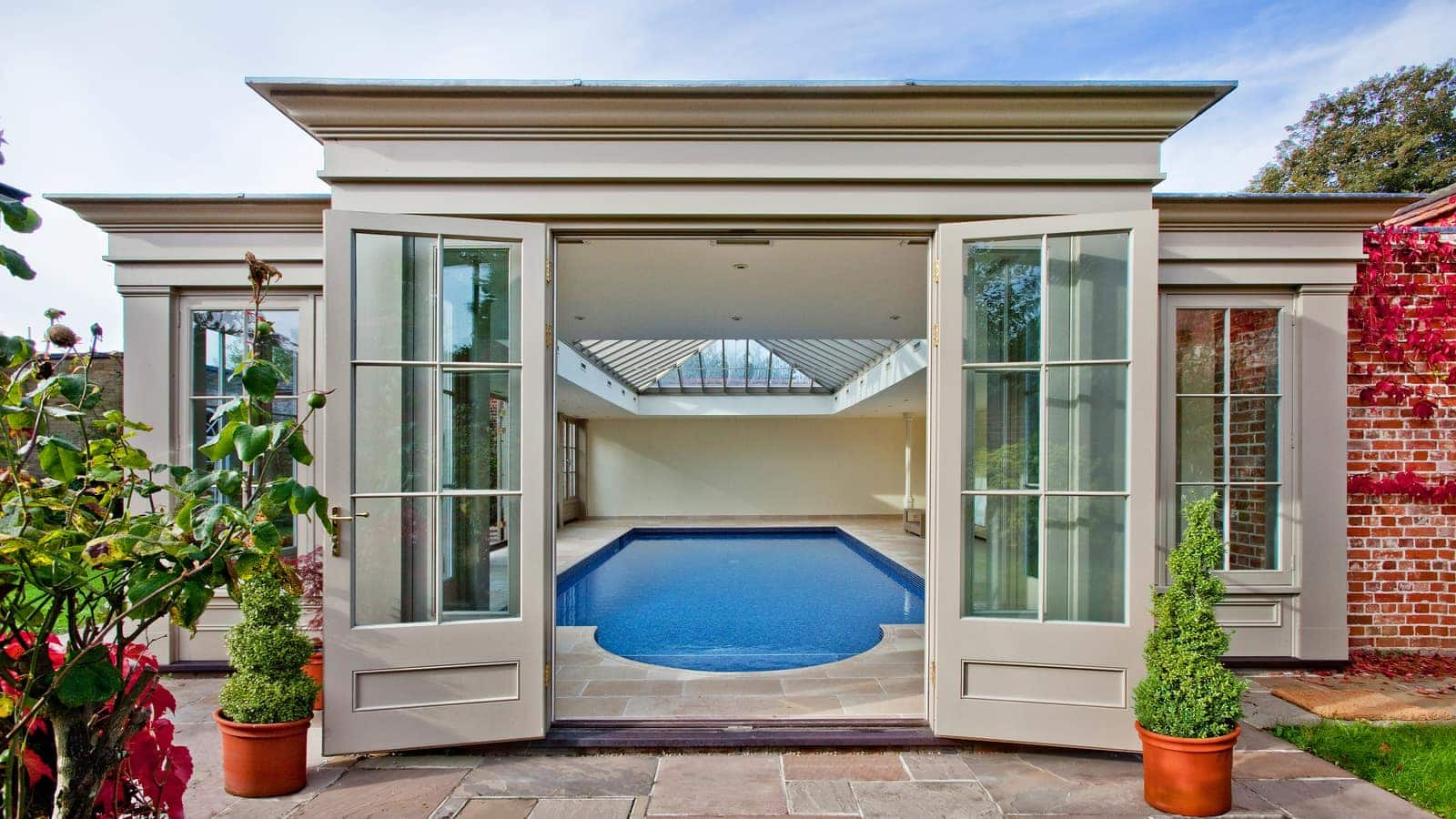 Pool house with wide opening doors allowing a cool breeze into the room
