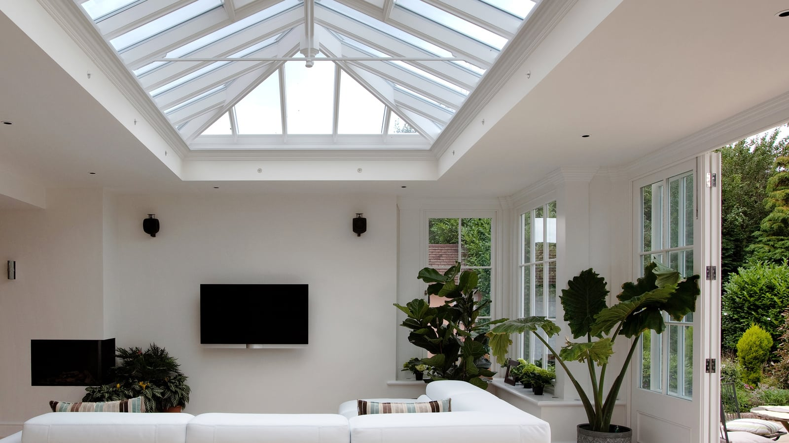 Light and welcoming seating area inside orangery beneath large roof lantern