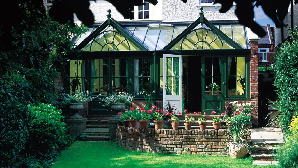 Double gabled timber conservatory, painted dark green to blend with garden