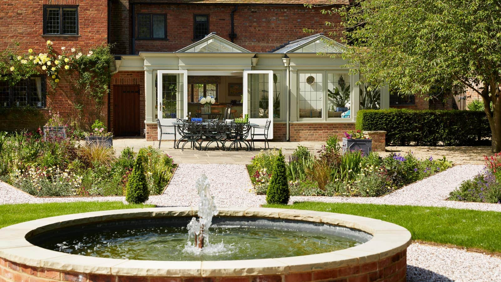 Long shot of twin gabled garden room with water feature in foreground