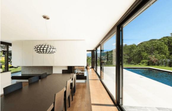 Glass sliding doors open up onto outdoor pool area