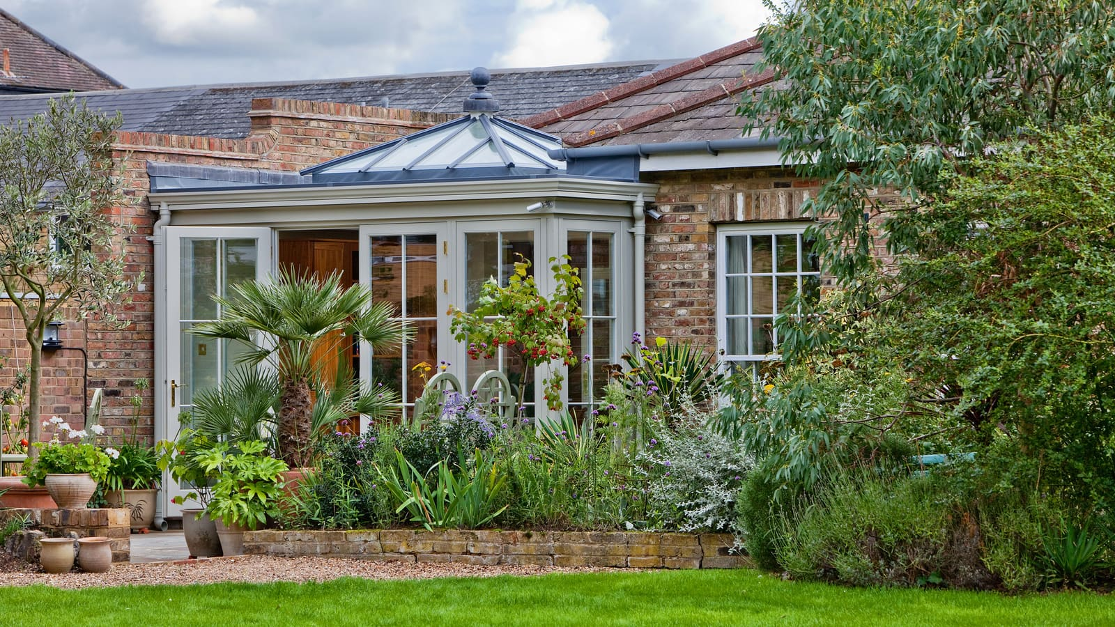 A timber orangery extension looking out onto a charming city courtyard garden