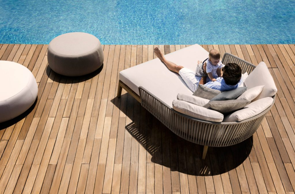 poolside furniture - father and son on wide day bed next to pool